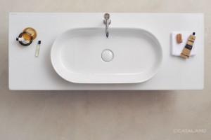 Bílá keramická deska Catalano Horizon s bílým umyvadlem.