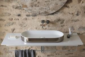 Bílá keramická deska Catalano Horizon se stříbrným umyvadlem.