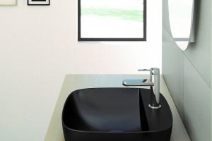 Černé matné umyvadlo Catalano Colori položené na desce.